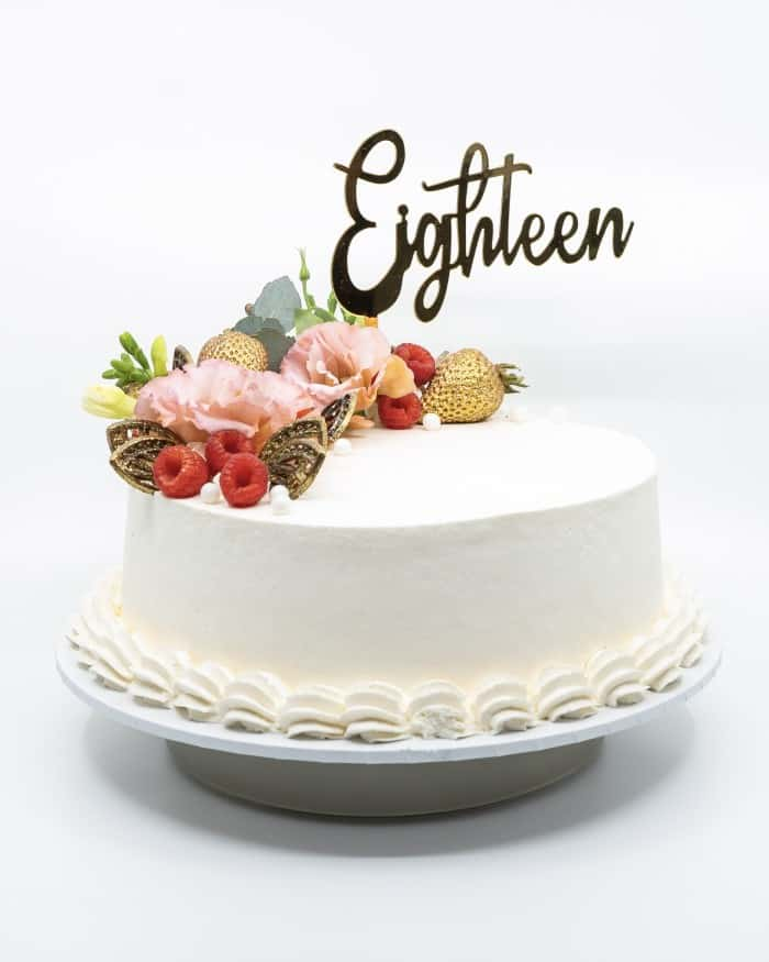 Solid vanilla buttercake with fresh flowers and fruit